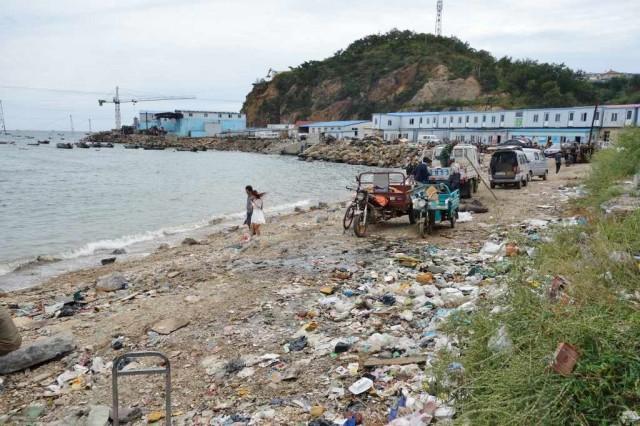ゴミだらけの海岸でデートするカップル 中国・大連